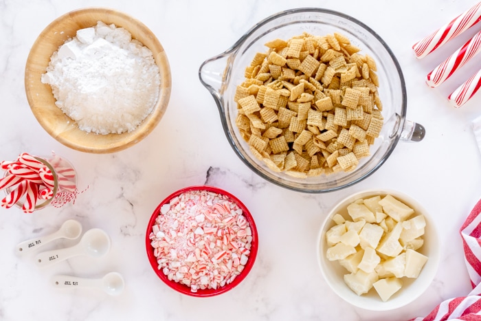 ingredients needed for peppermint muddy buddies: chex cereal, white chocolate, candy canes, powdered sugar