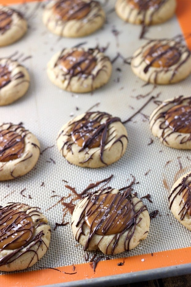 Salted Caramel Thumbprint Cookies - A soft sugar cookie filled with salted caramel and drizzled with melted semi sweet chocolate.