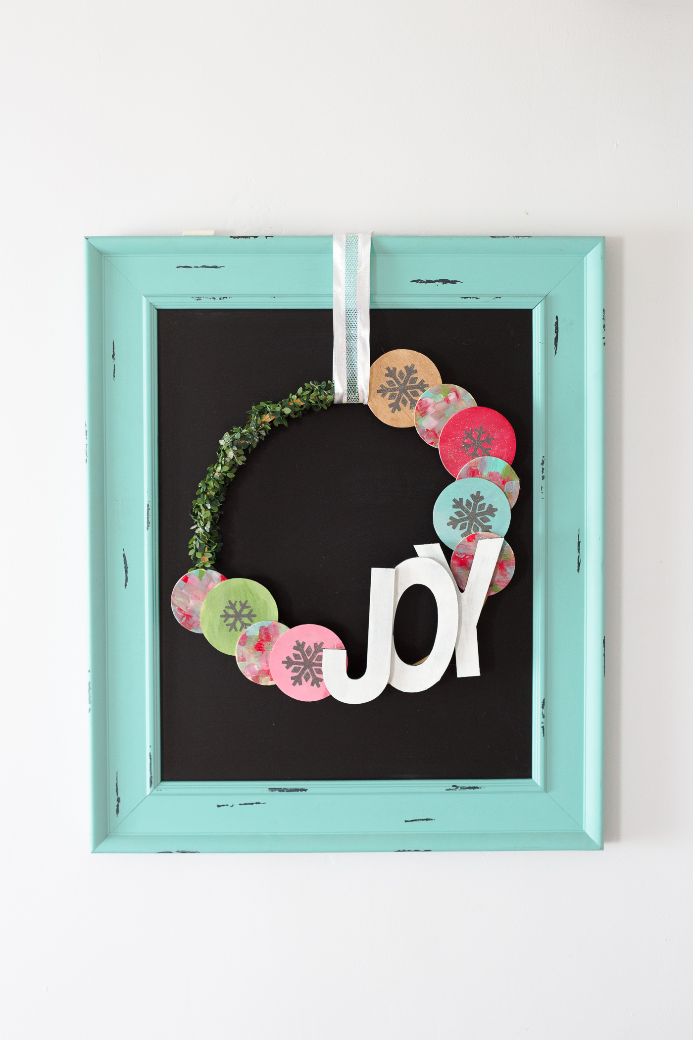Wooden Snowflake Christmas Wreath: a non traditional Christmas wreath with pops of color, glitter and greenery! Mix and match the colors for any Christmas decor.