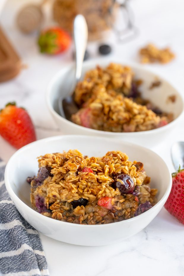 berry baked oatmeal in serving bowls with maple syrup