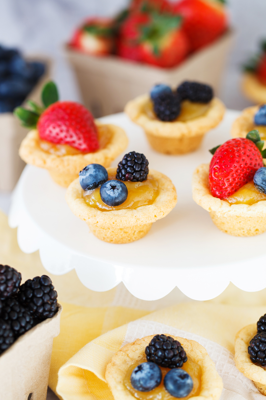 Sugar Cookie Lemon Tarts: a yummy sugar cookie tart filled with lemon curd, topped with fresh berries, and baked in a mini muffin tin.