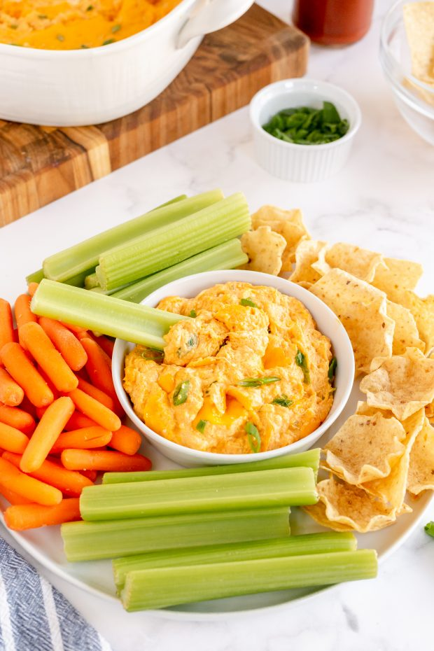 hot wing chicken dip on platter with chips and veggies