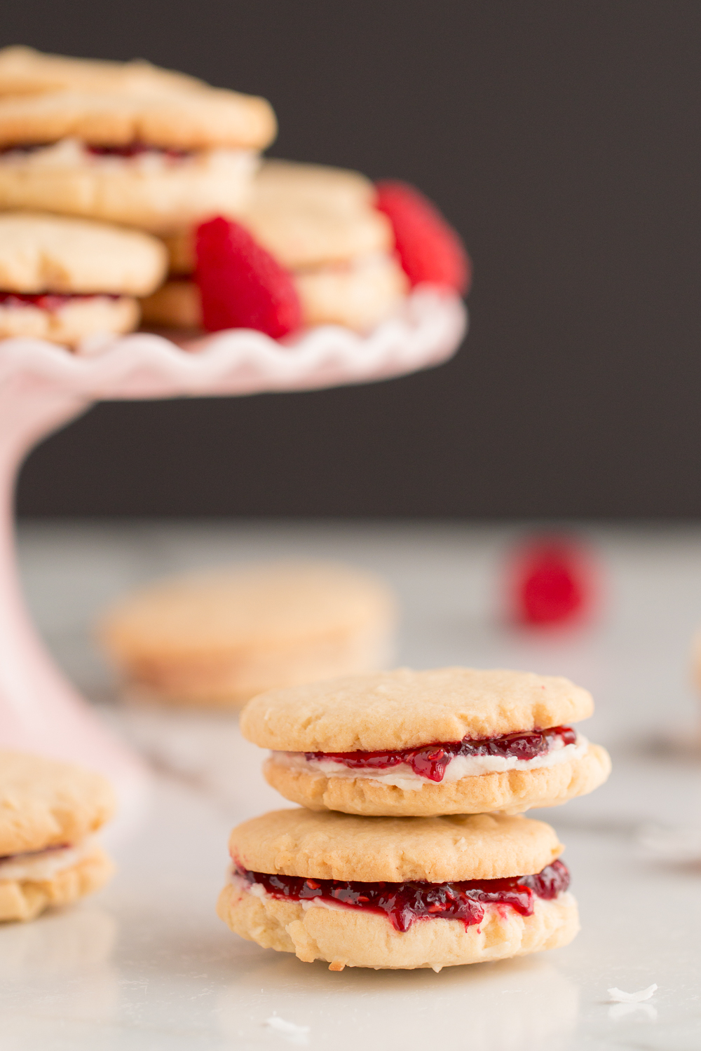Raspberry Coconut Cookies: a delicious raspberry jam filled sandwich cookie with bits of sweet coconut flavor. A pretty cookie perfect for Valentines Day, cookie exchanges, and more!