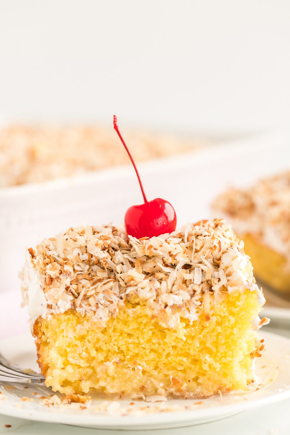 Coconut Cream Poke Cake: a delicious coconut cream poke cake filled with a coconut cream filling and topped with toasted coconut. It's a delicious creamy and flavorful cake perfect for a crowd.