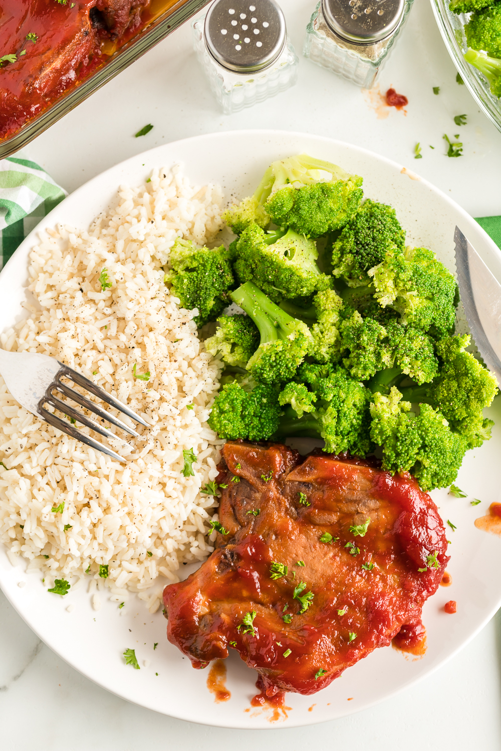 Oven Glazed Pork Chops: a delicious oven baked pork chop recipe that is marinated in a flavorful brown sugar marinade and then baked with a brown sugar and tomato based sauce. This recipe makes for a great weeknight meal!