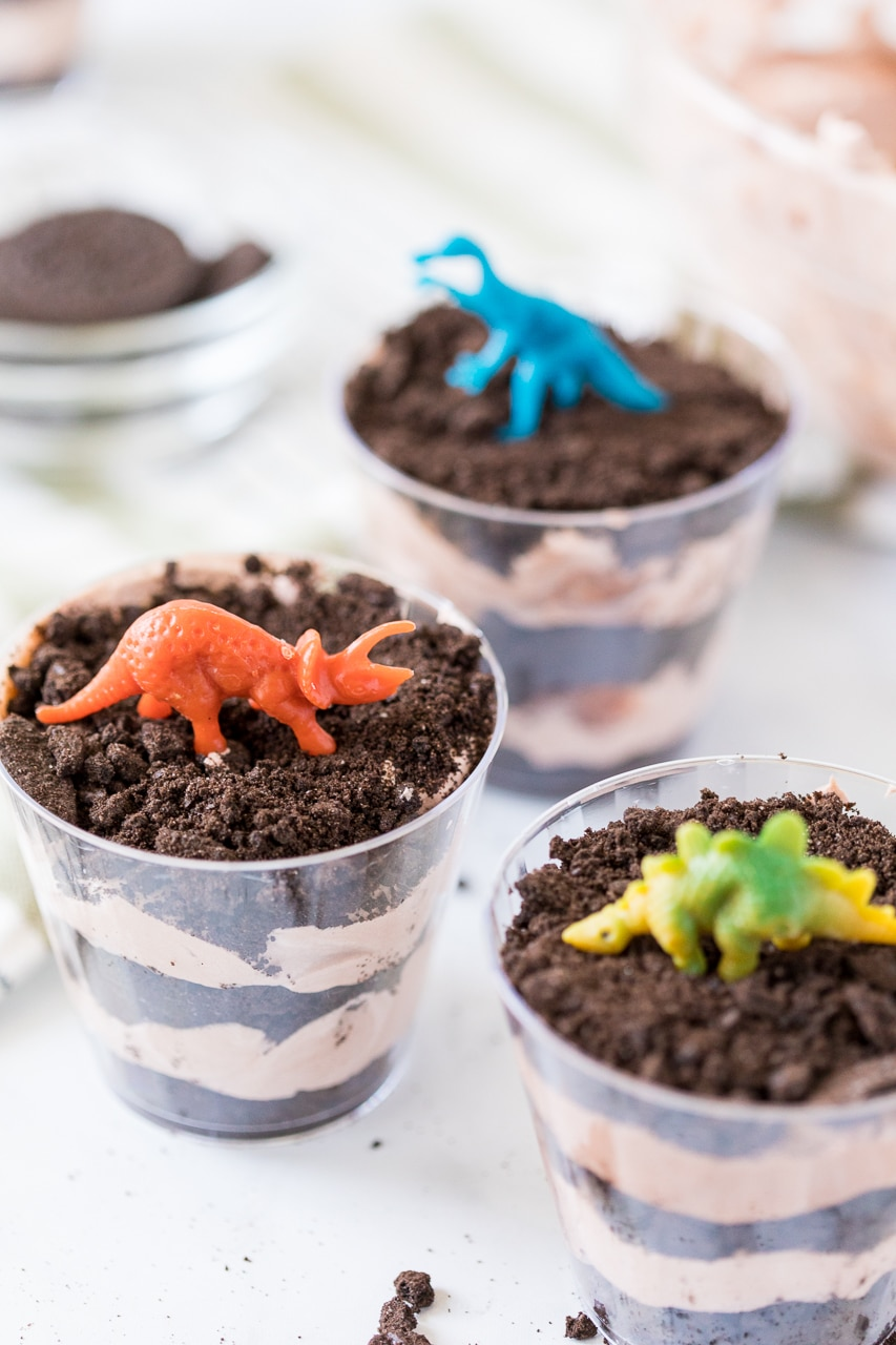 Dinosaur Dirt Cups: chocolate pudding and crushed Oreo cookies makes for a delicious layered chocolate dessert. Top it with a kid friendly dinosaur and you have a yummy and fun treat for any dino loving kid.