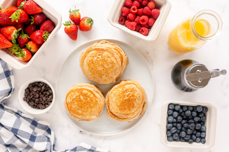 pancakes on plate with fruit toppings-strawberries, blueberries, raspberries
