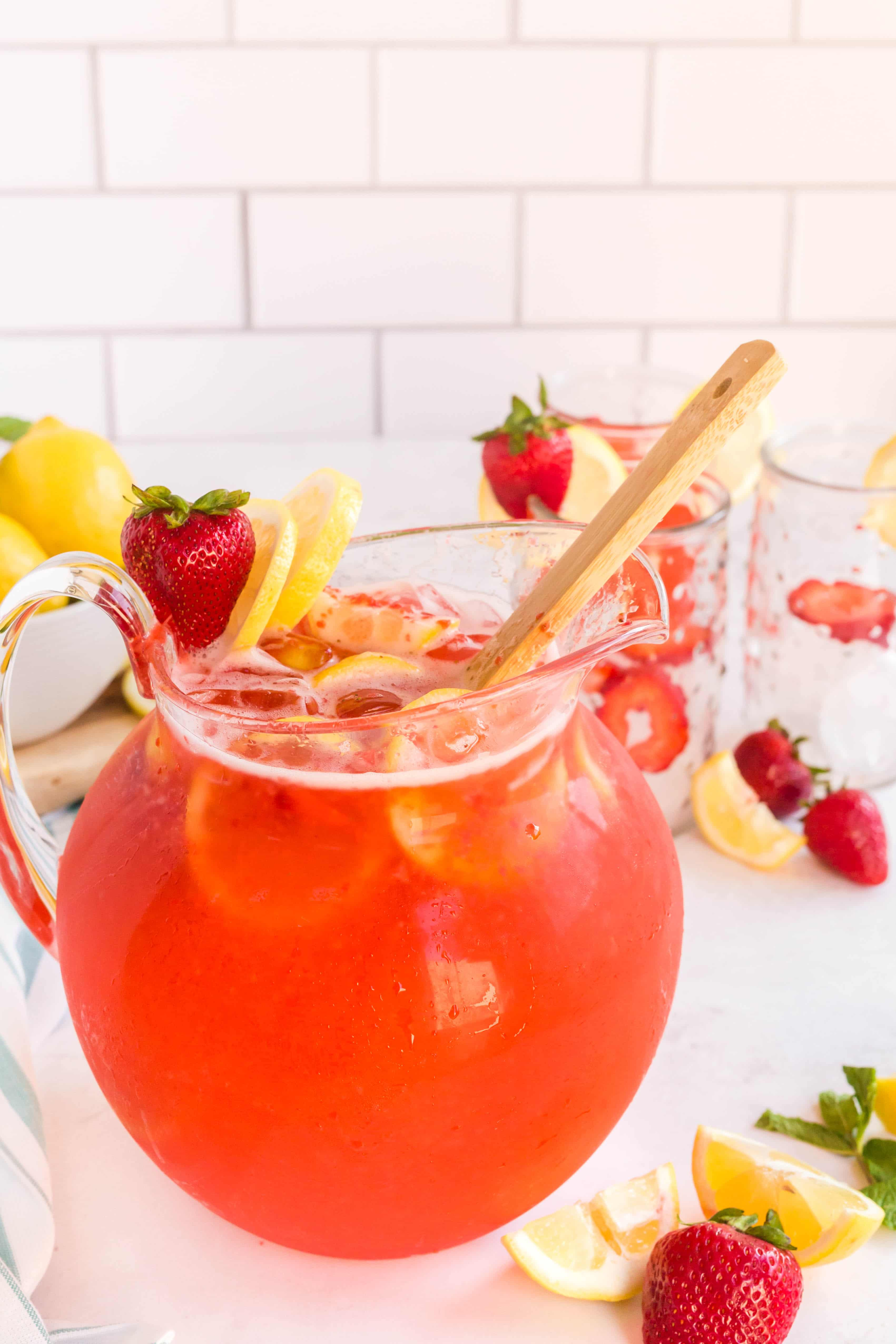 homemade strawberry lemonade in pitcher with garnishes