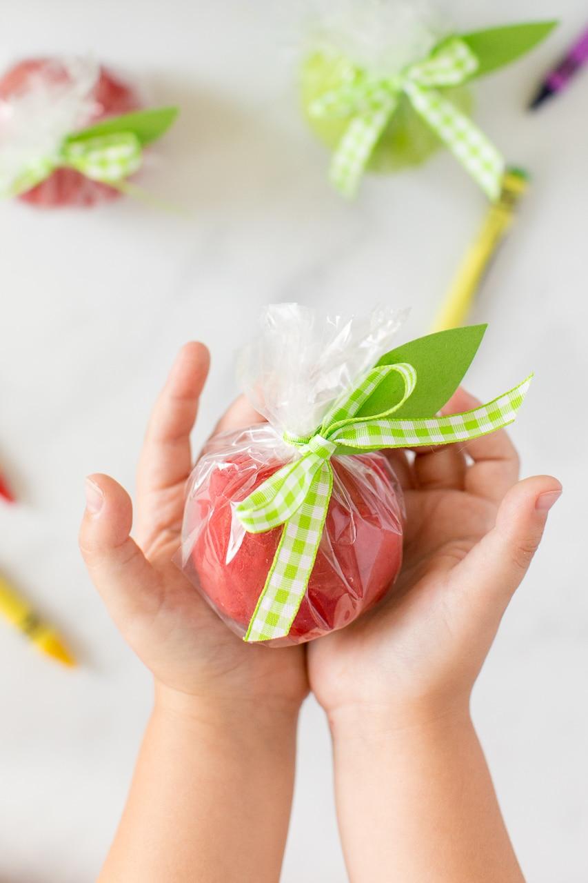 hand holding apple playdough in gift bag