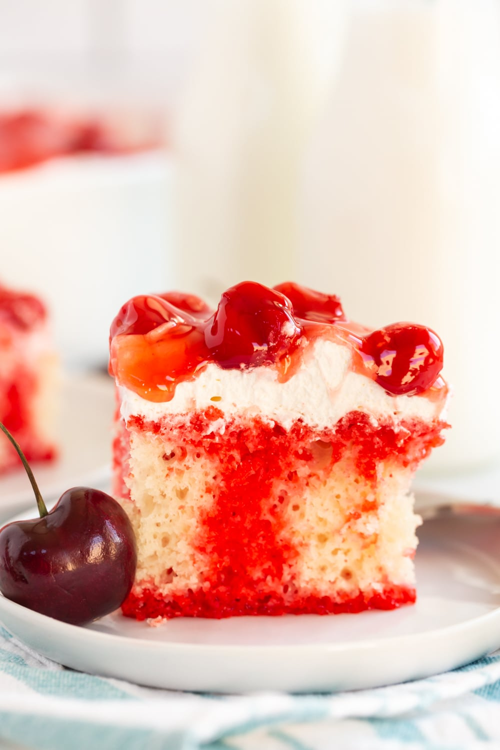 Cherry Poke Cake is a delicious simple dessert filled with cherry jello, whipped topping, and delicious cherry pie filling. It's simple and a crowd pleaser!