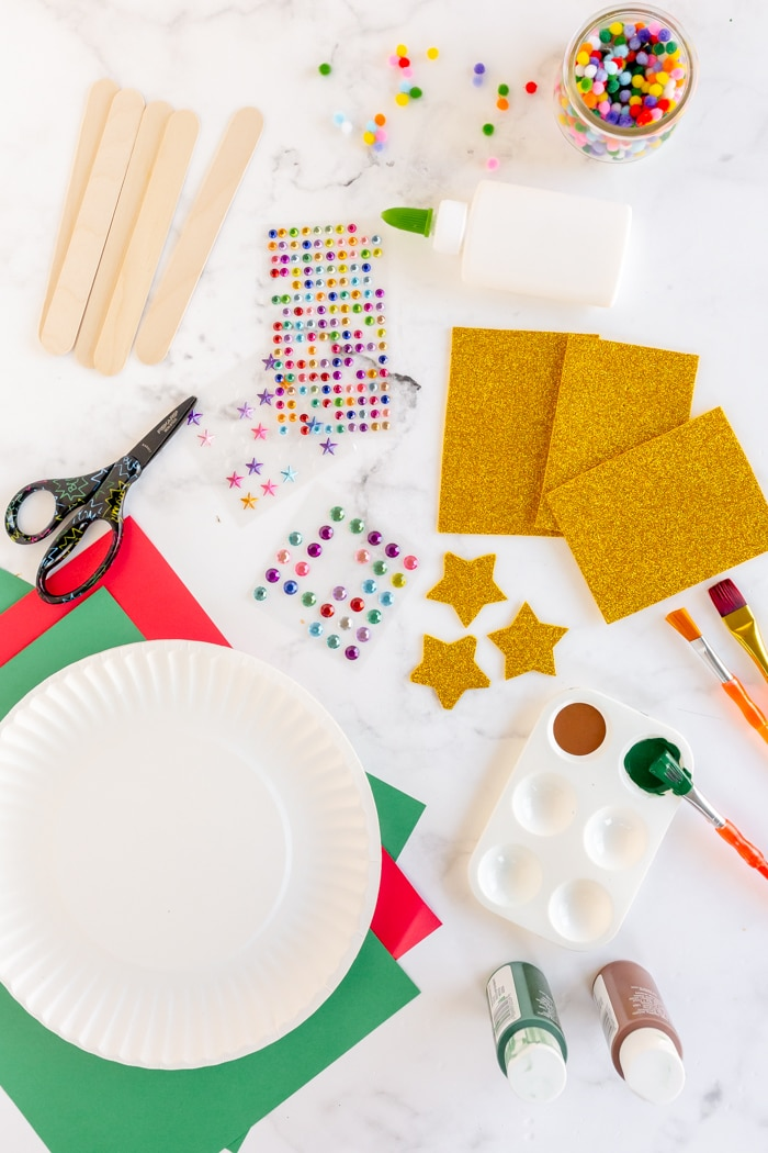 paper plate christmas tree supplies: paper plate, sequins, poms poms, glue, paint and popsicle sticks