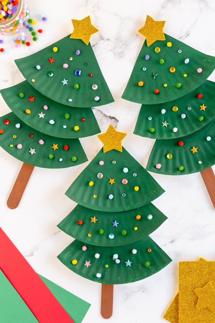 Completed painted green paper plate Christmas trees. decorated with poms poms, sequins and gold star.
