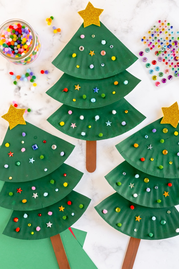 Three decorated paper plate Christmas tree crafts with mini poms poms and sequins