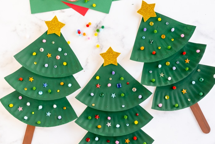 paper plate christmas tree decorated with colorful pom poms, sequins, and gold star on top.
