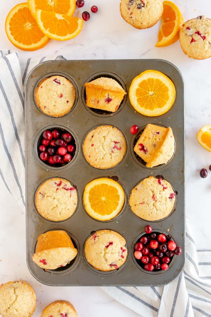 cranberry orange muffins in muffin tin with cranberries and orange slices as props