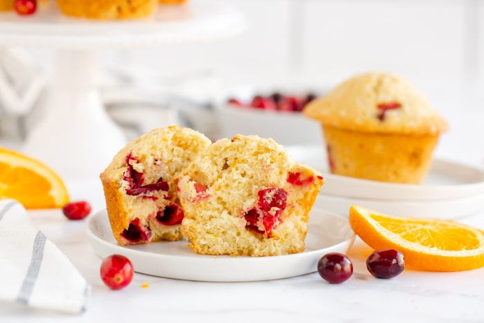cranberry orange muffin cut in half on white serving plate