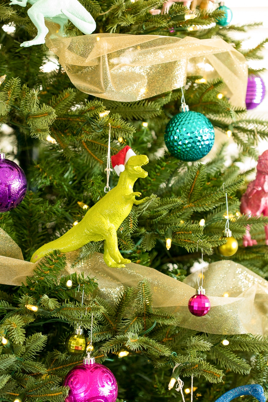 santa hat dinosaur on colorful christmas tree
