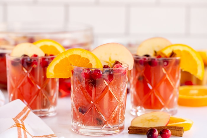 Thanksgiving Punch in individual clear serving glasses with garnishes of orange slices, cranberries and apple
