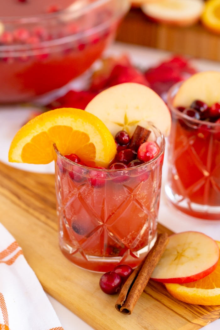 Thanksgiving Punch Recipe in individual clear glass garnished with apple slices, orange slice, and fresh cranberries