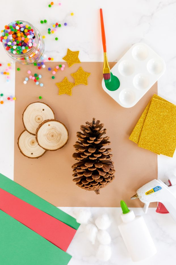 supplies needed: pinecone, wood slice, poms poms, paint and glue