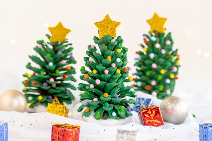 three colorful pom pom christmas trees with ornament and gift props