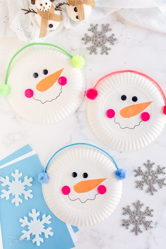 Three paper plate snowmen with earmuffs