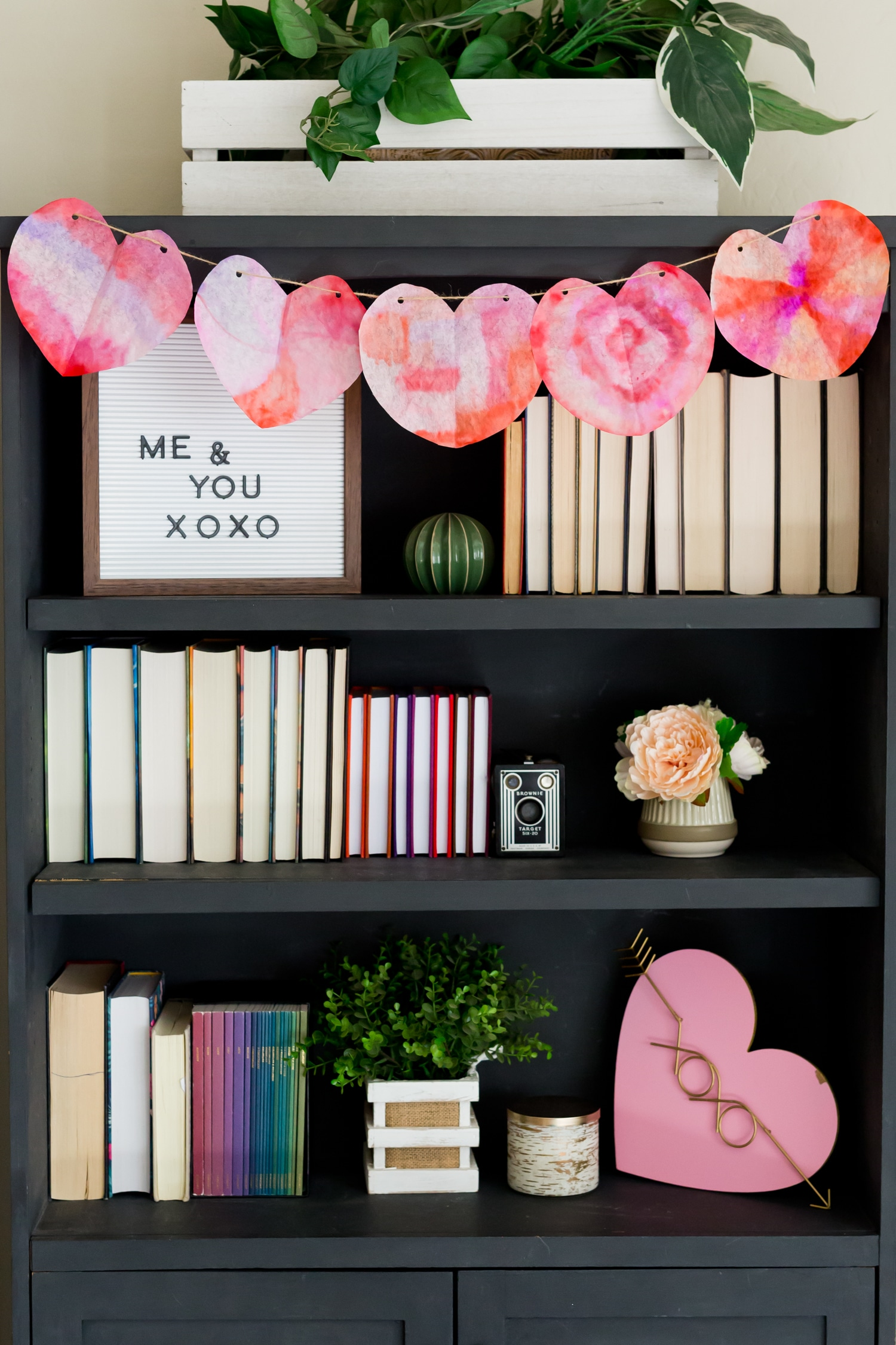 valentine's day garland on bookshefl