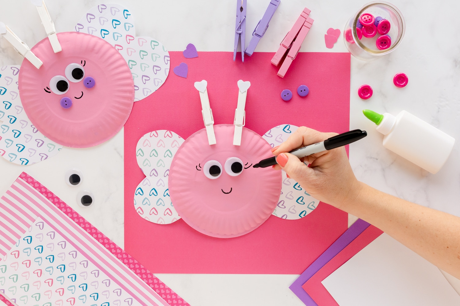 adding face to paper plate love bugs