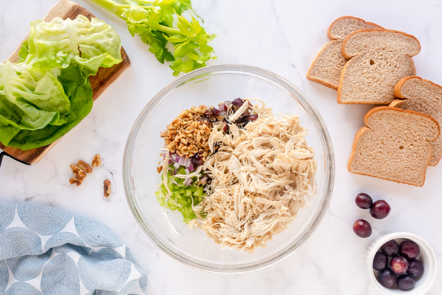 chicken salad ingredients in mixing bowl- chicken, grapes, walnuts, celery and red onion