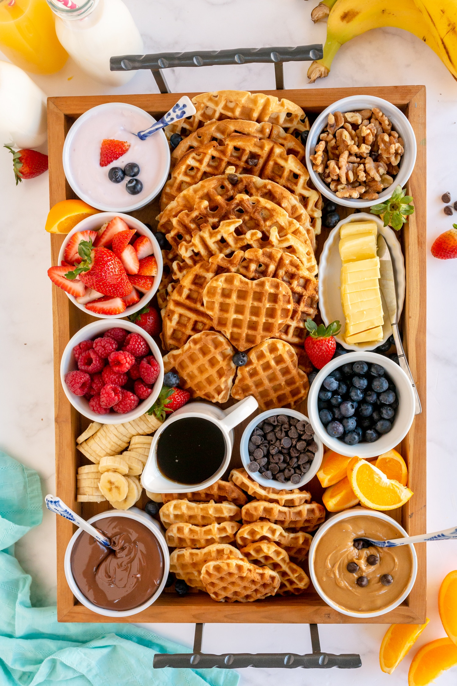 charcuterie board with waffles, toppings and syrups