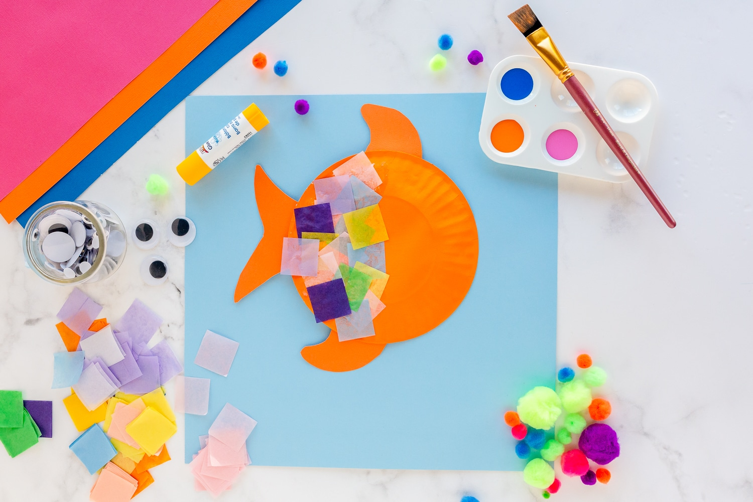 add tissue paper squares to painted paper plate with glue