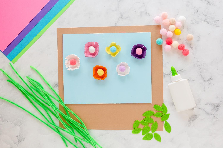 add pom pom to painted egg carton shaped flowers