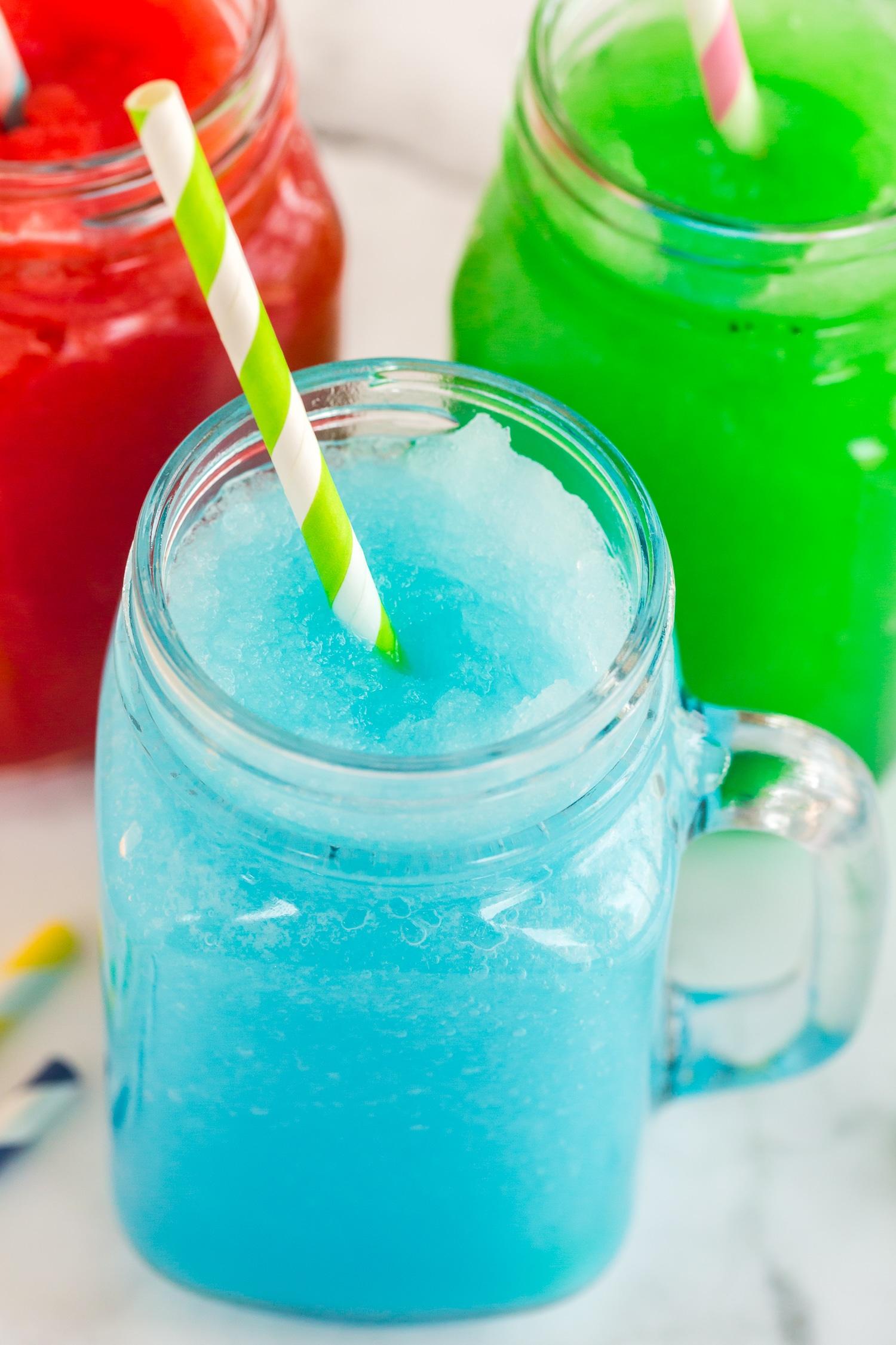 close up of blue slushie in mason jar with green straw