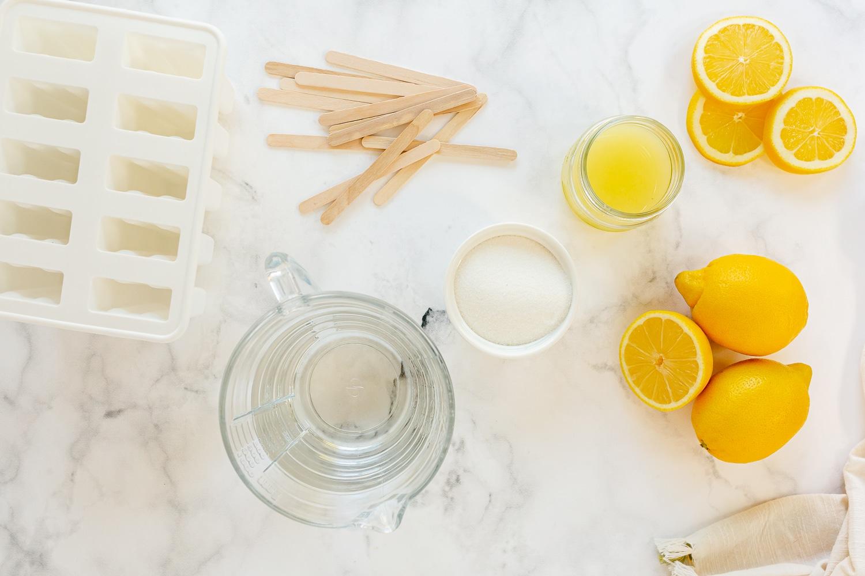ingredients for lemonade popsicles; lemon juice, water and sugar